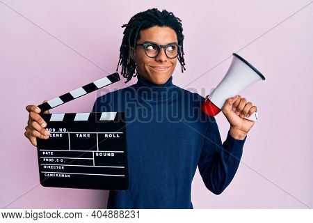 Young african american man holding video film clapboard and megaphone smiling looking to the side and staring away thinking.