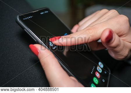 Rome, Italy - January 24 2021: Woman Tap On Tiktok App Icon On A Smartphone, Social Network Tech Add