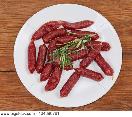 Small Thin Dry Cured Sausages In Natural Casing Decorated With Rosemary Twig On A White Dish On An O