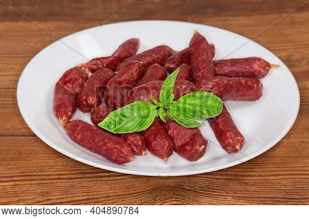 Small Thin Dry Cured Sausages In Natural Casing Decorated With Fresh Basil Twig On A White Dish On A