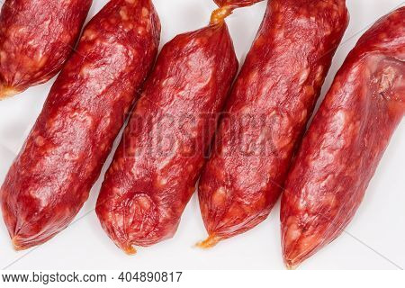 Small Thin Dry Cured Sausages In Natural Casing On A White Surface Close-up, Fragment Top View