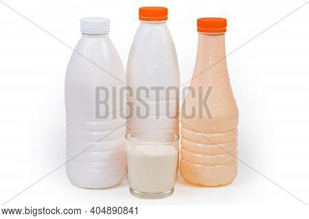 Fermented Baked Milk In A Glass Against The Plastic Bottles Of The Various Drinkable Fermented Dairy