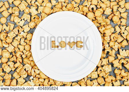 Scattered Alphabet Crackers And Word Love Spelled With Crackers On A White Plate
