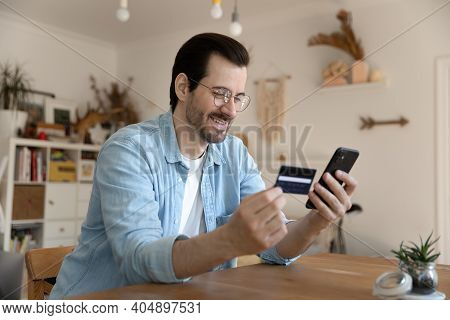 Millennial Man Using Card And Phone To Provide Payment Online