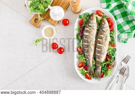 Seabass Or Sea Bass Fish Roasted And Fresh Vegetable Salad Of Tomatoes And Lettuce, Healthy Food For