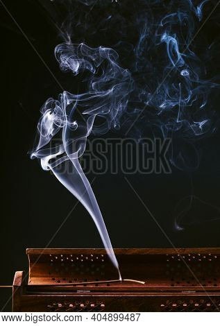 incense stick aroma with smoke  in a wooden handmade holder  isolated on background