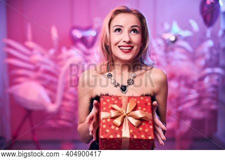 Joyous Elegant Woman Holding A Gift With Both Hands