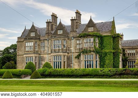 Killarney, Ireland - Jun 01, 2020: Muckross House And Gardens Against Cloudy Sky. It Is A Mansion De