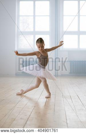 Little girl in tutu performing ballet dance alone in dance school