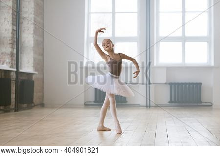Portrait of little girl in tutu dress and shoes preparing for a ballet performance