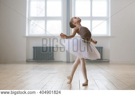 Young gifted dancer in tutu dress studying ballet dance in dance school