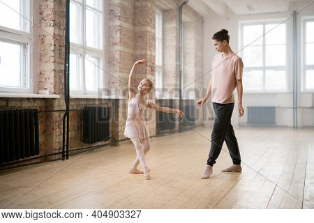 Young woman watching for the movements of her student while she dancing during classes in dance studio