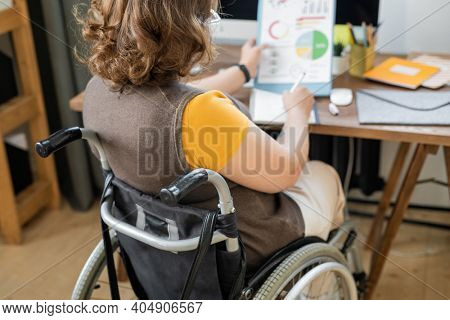 Back view of young disable female economist sitting in wheelchair in front of computer monitor and making notes while analyzing financial data