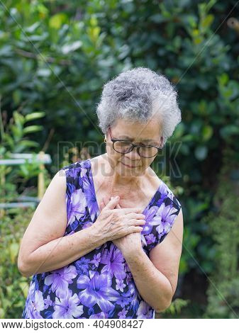 Portrait Of An Elderly Woman Having A Heart Attack. A Senior Woman Clutching Her Chest In Pain At Th