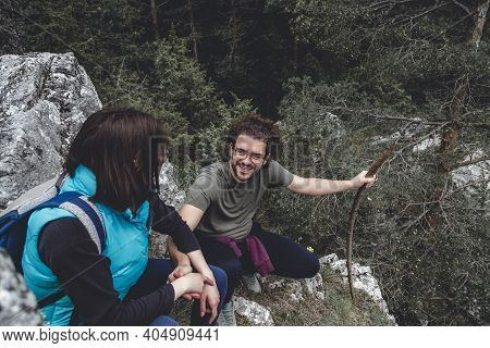 Young Couple Spending An Active Day Outdoors, Taking A Break While Mountaineering, Sitting At Some R