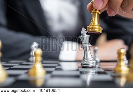 Businessman Hand Moving Gold Chess King Figure And Checkmate Enermy Or Opponent During Chessboard Co