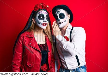 Couple wearing day of the dead costume over red hand on mouth telling secret rumor, whispering malicious talk conversation