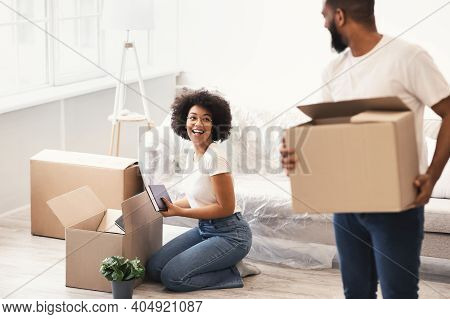 Black Spouses Packing For A House Move Carrying Packed Boxes Indoors. Young Family Housing, Real Est