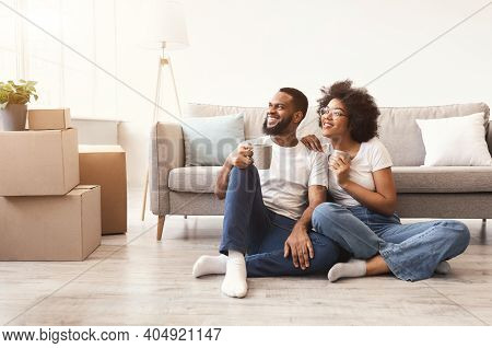 Moving House. Cheerful Black Spouses Enjoying Coffee Sitting Among Unpacked Moving Boxes In New Home