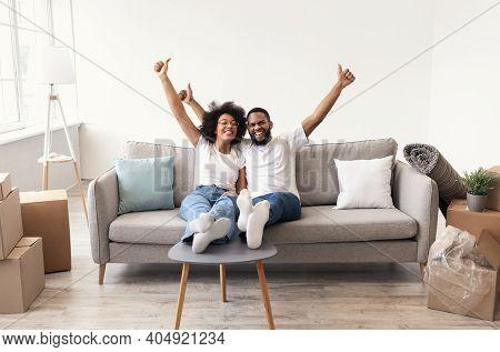 Family Housing. Joyful Black Couple Gesturing Thumbs Up Celebrating Moving To New Apartment, Sitting