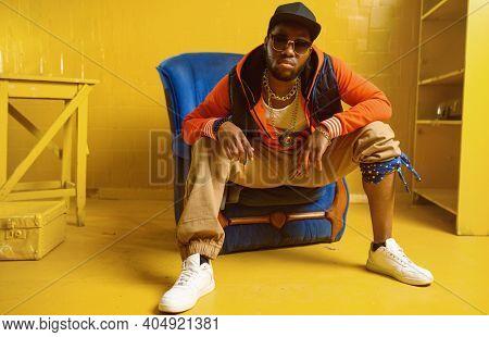 Rapper posing in chair in studio with yellow tones
