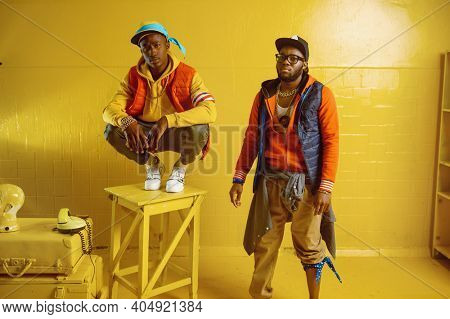 Two stylish rappers in studio, yellow background