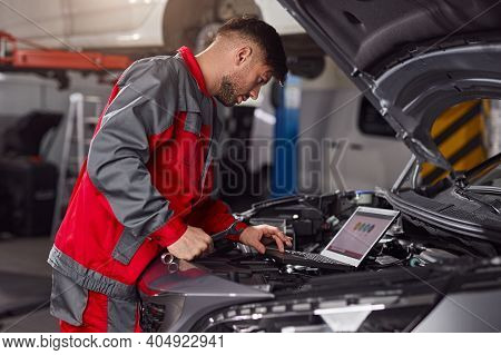 Side View Of Male Mechanic In Uniform Browsing Data On Laptop While Repairing Motor Of Vehicle Durin
