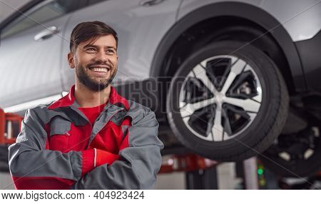 Confident Smiling Adult Bearded Repairman With Arms Crossed Looking Away While Standing Near Suspend
