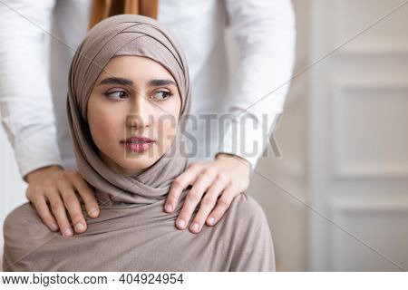 Arab Husband Threatening Scared Wife In Hijab Touching Her Shoulders Standing Behind Her Back At Hom