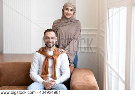 Cheerful Young Muslim Family Couple Posing At Home, Arab Wife In Hijab Standing Near Loving Husband,