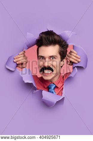 Young Man With Fake Mustache Smiling Maniacally And Looking At Camera While Ripping Hole In Violet P