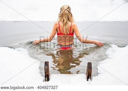 Beautiful Blonde Hair Girl With Red Swimsuit Bathing And Swimming In The Cold Water Of A Lake Or Riv
