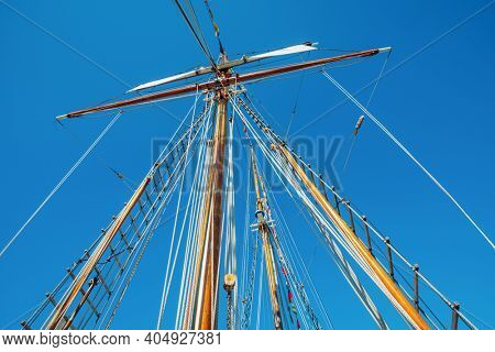 Old sailing ship wood mast, rigging of a sailing ship detail against blue sky