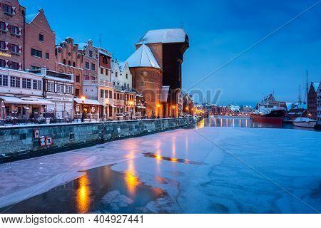 Gdansk, Poland - January 17, 2021: Medieval port crane in Gdansk at Motlawa river in snowy winter, Poland