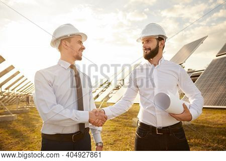 Happy Bearded Men With Draft Smiling And Shaking Hands While Making Agreement During Work On Solar P