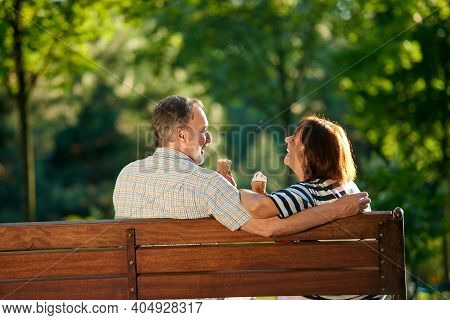 Happy Retired Couple Eating Ice-cream And Laughing. Senior Caucasian Man And Woman Sit On The Bench