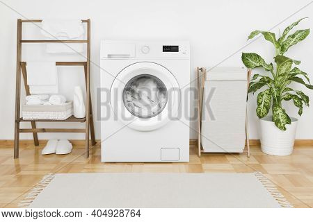 Interior Of Laundry Room With Modern Washing Machine And Textile