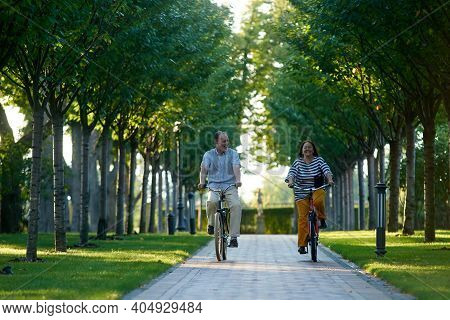 Happy Retired Couple Cyling In The Park. Grandfather And Grandmother Rides On Bikes.