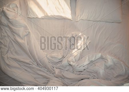Top View White Bed Pillows And Bed Blanket Bed Sheets In Bed Room With Sun Light From Window After W