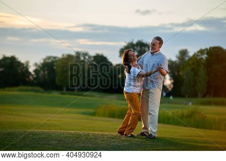 Mature Couple Dancing Tango Outdoors. Man And Woman On The Green Field.