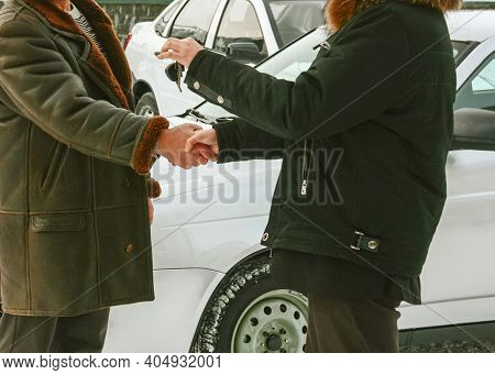 Seller Or Car Salesman And Customer Next To Dealership, They Shaking Hands, Hands Over The Car Key