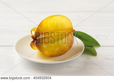 One Whole Ripe Carambola Or Star Fruit On A Saucer Over White Wood Table. Ingredient For Cocktails,