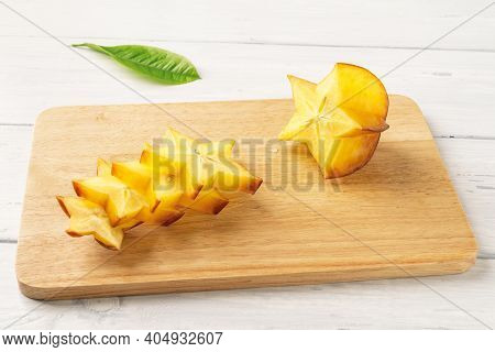 Slises And Half Of Ripe Juicy Carambola Or Star Fruit On A Wooden Cutting Board. Ingredient For Cock