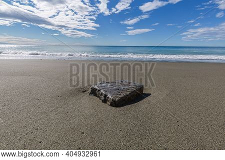 Blue Sea Water Waves With White Foam And Bubbles Washes The Beach. Wet Stone On The Beach Like Place