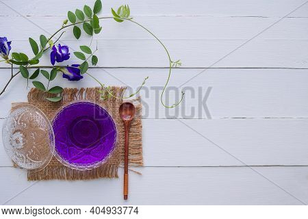 Anchan Flower Juice Or Blue Pea Flower Herbal Tea, Butterfly Pea In Glass Cup With Wooden Spoon On W