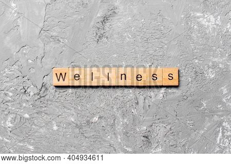Wellness Word Written On Wood Block. Wellness Text On Cement Table For Your Desing, Concept