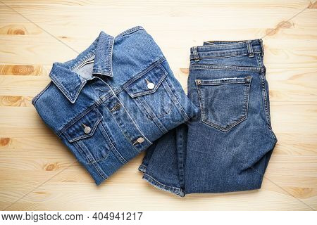 Jeans Women's Jacket And Denim Pants On The Wooden Background, Top View.