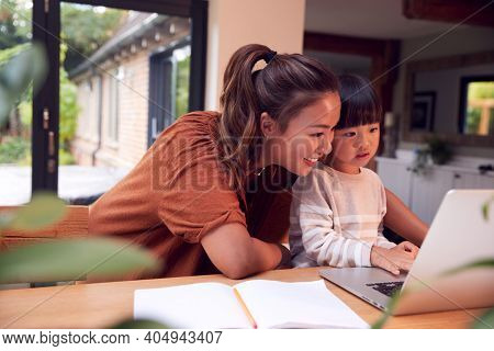 Asian Mother Helping Home Schooling Son Working At Table In Kitchen On Laptop