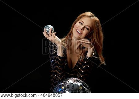 Glamour Model Posing On Near Disco Ball. Smiling Gorgeous Blonde Woman In A Black Sequins Dress For