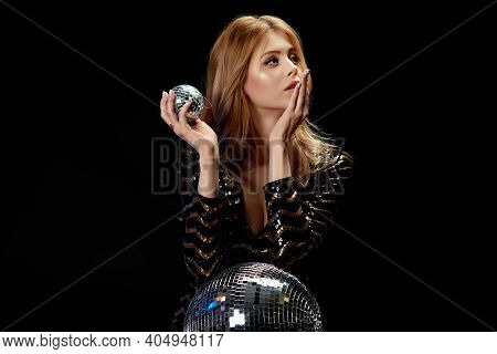 Glamour Model Posing On Near Disco Ball. Gorgeous Curly Blonde Woman In A Black Sequins Dress For Pa